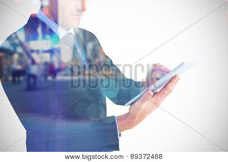 Mid section of a businessman using digital tablet against blurry new york street