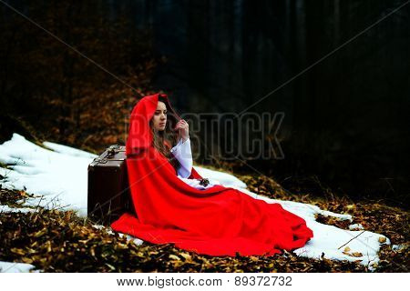beautiful woman with red cloak in the woods, sitting on ground