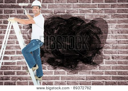 Portrait of man on ladder painting with roller against red brick wall