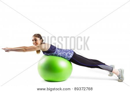 Fit woman exercising on exercise ball on white background