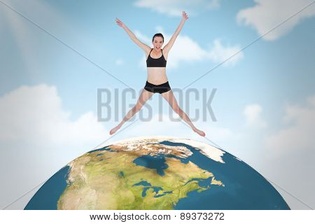 Full length of a sporty young woman jumping against blue sky