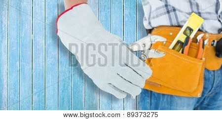 Technician using pliers over white background against wooden planks