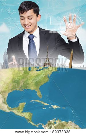Smiling businessman holding and pointing against blue sky