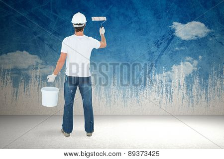 Rear view of man using paint roller against painted sky