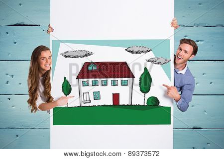Happy young couple with blank board against painted blue wooden planks