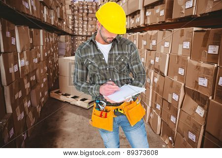 Manual worker writing on clipboard against boxes in warehouse