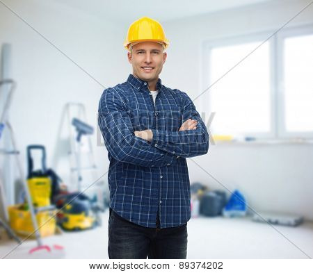 repair, construction, building, people and maintenance concept - smiling male builder or manual worker in helmet over room with work equipment background