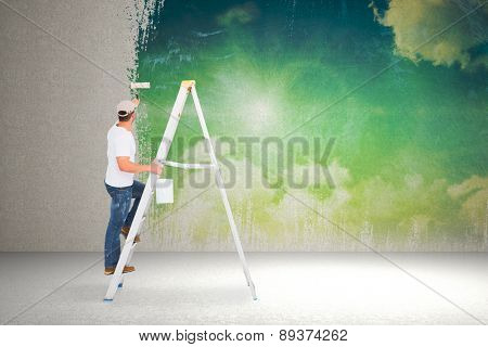 Handyman climbing ladder while using paint roller against painted sky