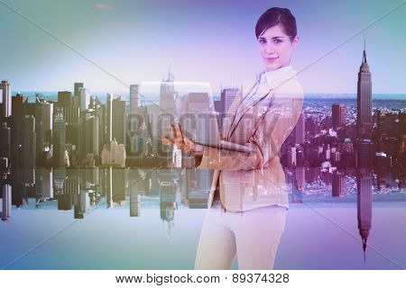 Confident young businesswoman with laptop against mirror image of city skyline