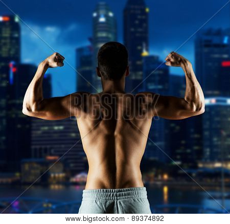 sport, fitness, bodybuilding, strength and people concept - young man or bodybuilder showing biceps over night city background