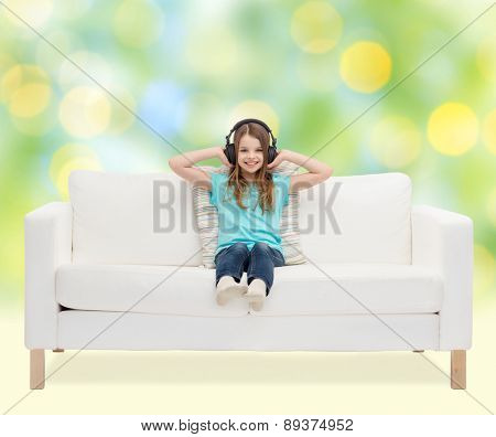 leisure, technology, music and childhood concept - smiling little girl in headphones listening to music sitting on sofa over green lights background