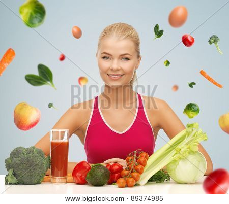 people, healthy eating, vegetarian and health care concept - happy woman with organic food and falling vegetables over gray background