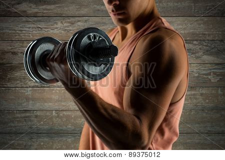 sport, fitness, weightlifting, bodybuilding and people concept - close up of young man with dumbbell flexing biceps over wooden wall background