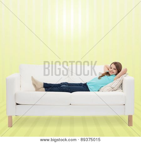 home, leisure, people and happiness concept - smiling little girl lying on sofa over yellow striped background