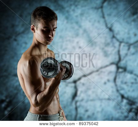 sport, fitness, weightlifting, bodybuilding and people concept - young man with dumbbell flexing biceps over concrete wall background