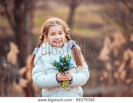 cute happy little girl smiling and holding a bouquet of snowdrops