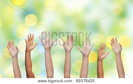 gesture, greeting, charity and body parts concept - people waving hands over green lights background