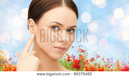people, beauty, hearing and healthcare concept - face of beautiful woman touching her ear over poppy field background