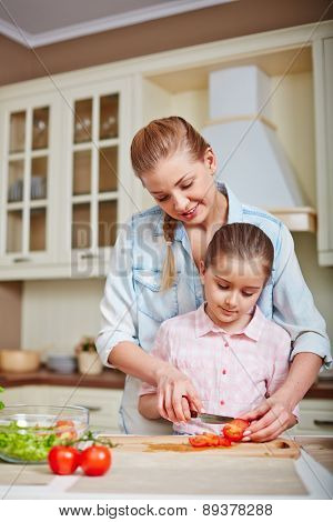 Young female and her cute daughter cutting tomatoes together