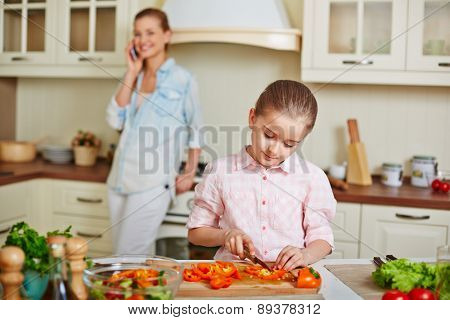 Little girl cutting fresh pepper with her mother calling on background