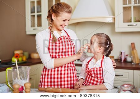 Cute girl and her mother in aprons having fun while going to make pastry