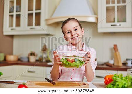 Cute girl with bowl of salad looking at camera