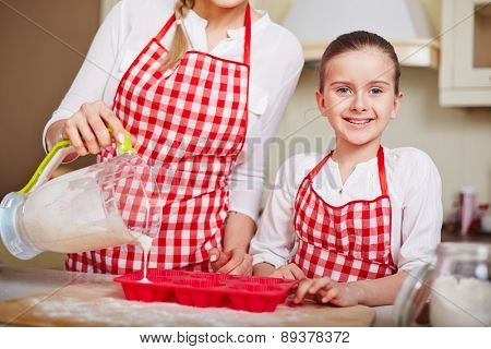Adorable girl looking at camera while her mother filling in muffin forms with liquid dough