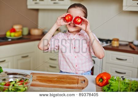 Smiling girl holding fresh tomatoes by her eyes