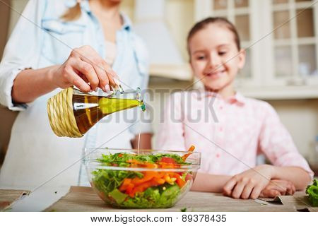 Young woman dripping olive oil into bowl with fresh vegetable salad