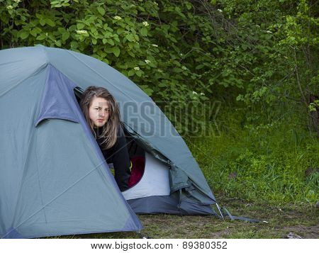 A Young Girl Looks Out Of The Tent.