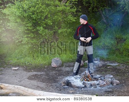 A Man Stands Near A Fire.