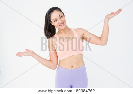Fit brunette presenting with her hands on white background