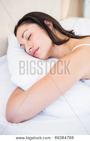 Pretty brunette sleeping on bed at home