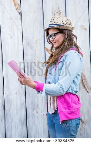 Pretty brunette reading book against wooden planks