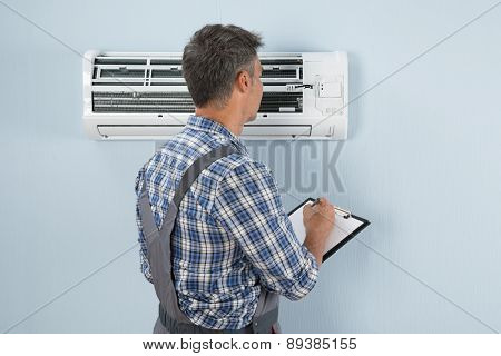 Technician With Clipboard Looking At Air Conditioner
