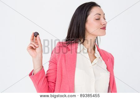 Pretty brunette holding piece of chocolate on white background