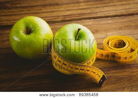 Green apples with measuring tape on wooden background
