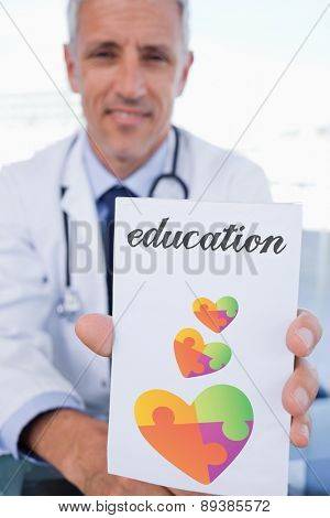 The word education and portrait of a male doctor showing a blank prescription sheet against autism awareness heart