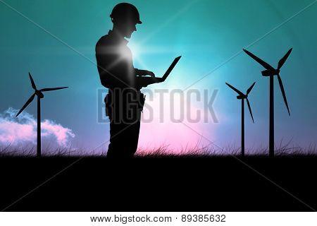 Full length of repairman using laptop against magical sky