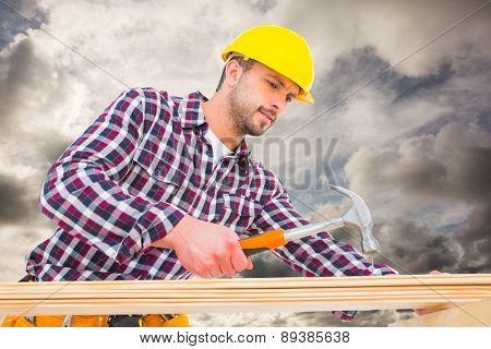 Handyman using hammer on wood against blue sky with white clouds