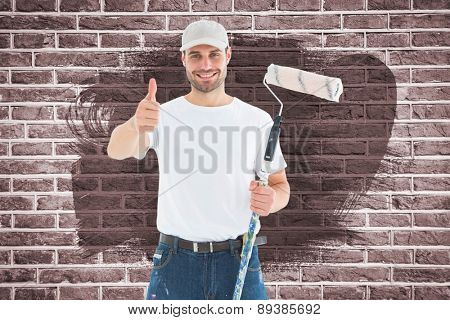 Happy man with paint roller gesturing thumbs up against red brick wall