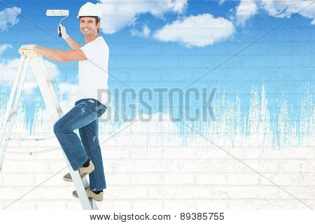 Portrait of man on ladder painting with roller against blue sky