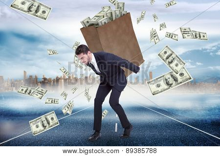Businessman carrying bag of dollars against large city on the horizon