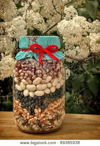 Country style jar of beans with lilacs