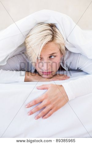 Sad blonde woman lying on the bed in her bedroom