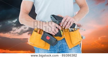 Repairman holding handheld drill against orange and blue sky with clouds