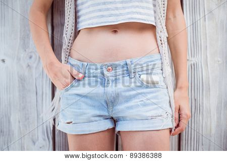 Pretty blonde woman wearing shorts on wooden background