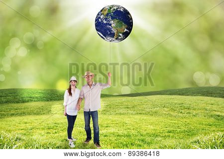 Smiling couple both wearing hats against field with glowing sky