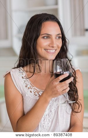 Pretty brunette having a glass of wine in the kitchen
