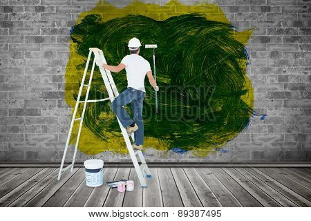 Man on ladder painting with roller against grey room